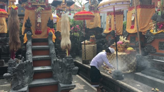 balinese man giving religious offering on galungan and kuningan holidays - religious celebration stock videos & royalty-free footage