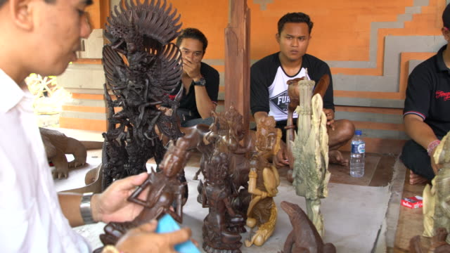 stockvideo's en b-roll-footage met balinese men hand-crafting wood  relief carvings and wood sculptures in bali, indonesia - in kleermakerszit