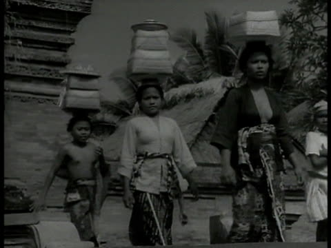 balinese people, women, children walking w/ temple roof bg, some w/ packages on heads. vs balinese dancers in front of temple, dancer holding bow &... - balinese culture stock videos & royalty-free footage