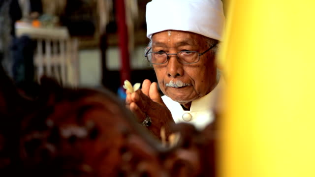 balinese priest at alter with incense performing wedding - priest stock videos & royalty-free footage