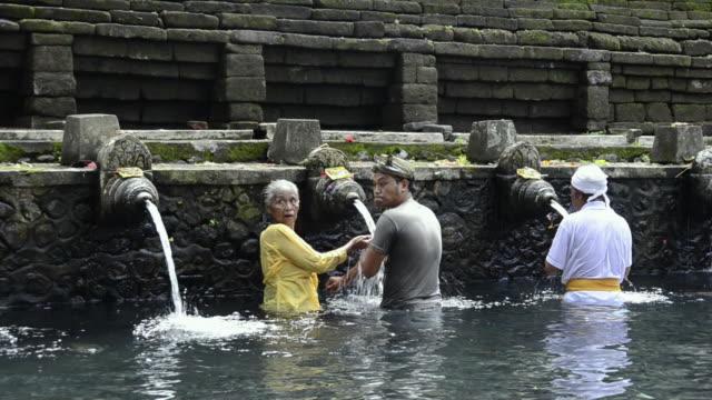 ms pan balinese take bath in holy spring of pura tirta empul / tampaksiring, bali, indonesia - acqua santa video stock e b–roll