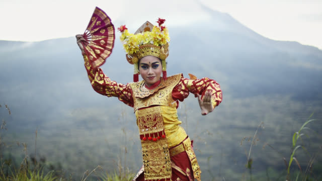 balinese traditional legong dancer performing in front of mount batur volcano - bali stock videos & royalty-free footage