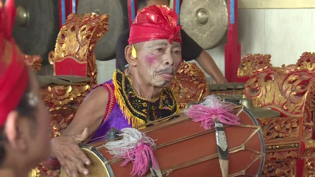 vídeos de stock e filmes b-roll de balinese women dressed in gold bodices dance to rhythmic drumming while waving fans as men in purple outfits sit cross legged around them jiggling... - cross legged
