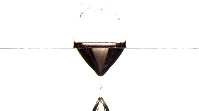 vídeos de stock, filmes e b-roll de a ball drops into water in slow motion, sending up a splash of water. - tensão de superfície