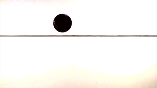 vídeos de stock, filmes e b-roll de a ball falls into a layer of water at an angle and splashes. - tensão de superfície