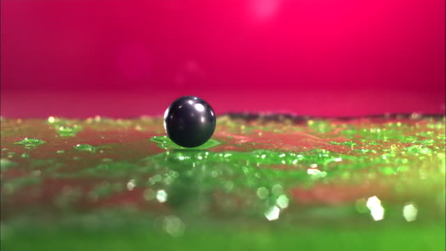 a ball falls onto a green rigid gelatin surface and bounces. - gelatin stock videos & royalty-free footage