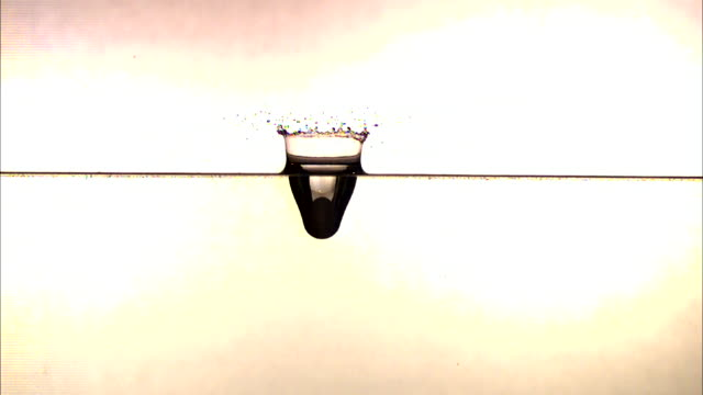 vídeos de stock, filmes e b-roll de a ball falls straight down into a layer of water and splashes. - tensão de superfície