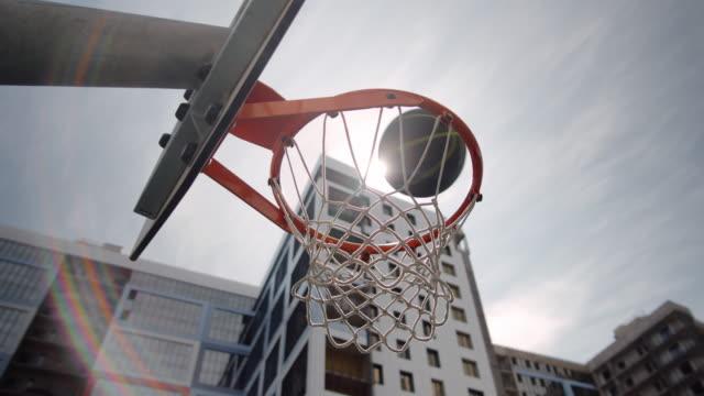 vidéos et rushes de ball flying through basketball hoop on outdoor court in the city - terrain de jeu