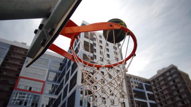 ball going through basketball hoop on outdoor court - basketboll boll bildbanksvideor och videomaterial från bakom kulisserna