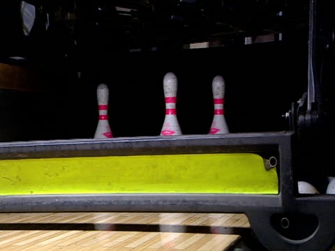 ball is bowled down lane knocking over seven pins in game of ten-pin bowling - bowling ball stock videos & royalty-free footage