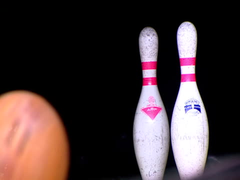 ball is bowled down lane knocking over two pins to make spare in ten-pin bowling - bowling ball stock videos & royalty-free footage