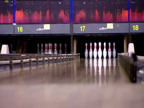 vídeos de stock, filmes e b-roll de ball is bowled down lane to score strike in ten-pin bowling - cancha de jogo de boliche