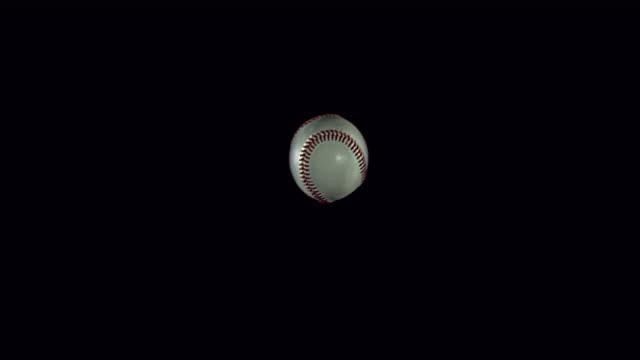 Ball of Baseball breaking Pane of Glass against Black Background, Slow Motion 4K