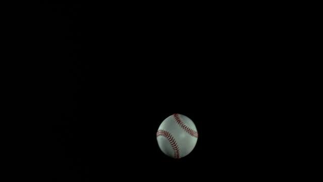 ball of baseball breaking pane of glass against black background, slow motion 4k - spielball stock-videos und b-roll-filmmaterial