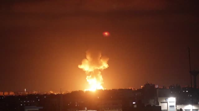 ball of fire illuminates the horizon during an israeli airstrike in rafah in the southern gaza strip, while rockets launched from the palestinian... - israel stock videos & royalty-free footage