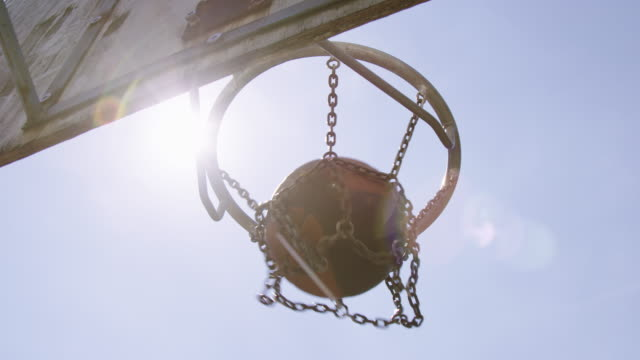 ball durch basketballkorb am sonnigen tag - basketball stock-videos und b-roll-filmmaterial