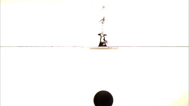 vídeos de stock, filmes e b-roll de a ball slowly drops into clear water. - tensão de superfície