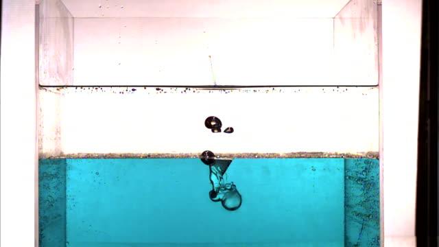 vídeos de stock, filmes e b-roll de a ball splashes through a clear liquid and a blue liquid as bubbles rise to the surface. - tensão de superfície