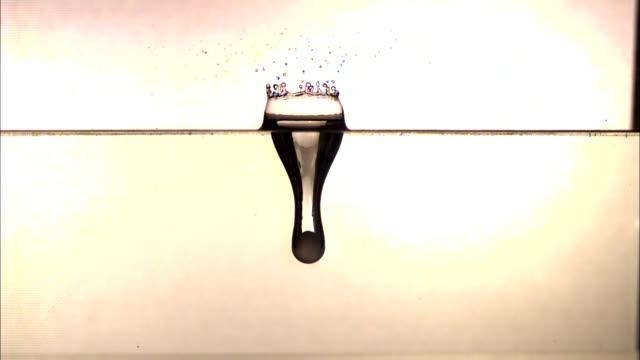 a ball splashes through a clear liquid and sinks. - 沈没する点の映像素材/bロール
