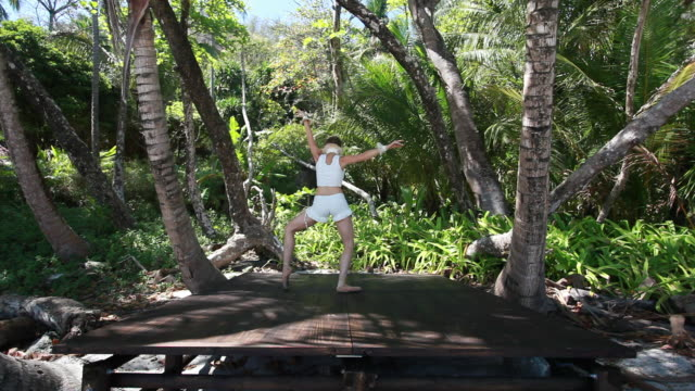 vídeos de stock, filmes e b-roll de ms ballerina dancer dancing in point shoes on wooden stage between trees / montezuma, nicoya peninsula, costa rica - kelly mason videos