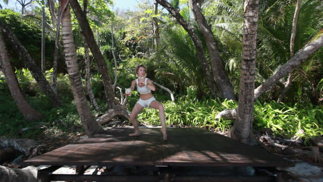 vídeos de stock e filmes b-roll de ms ballerina dancer dancing in point shoes on wooden stage surrounded by palm trees / montezuma, nicoya peninsula, costa rica - andar em bico de pés