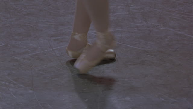a ballerina dances across a floor in ballet shoes. - ballet shoe stock videos and b-roll footage
