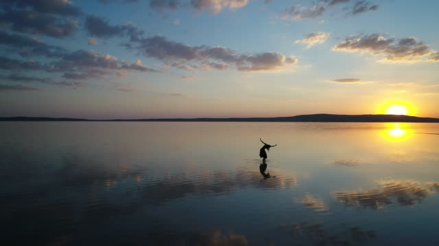 ballerina dancing on the lake at sunset. aerial taken - ballet dancing stock videos & royalty-free footage