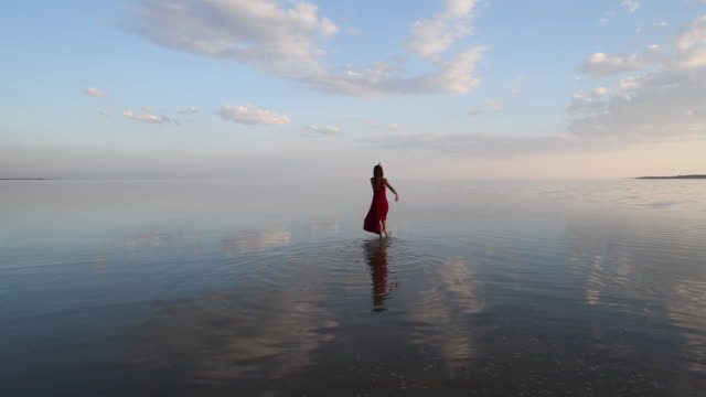 Ballerina dancing on the lake with red dressed