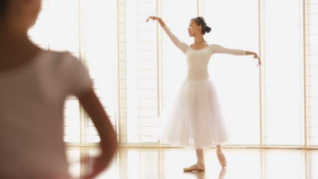 ws ballerina dancing with young girls dancing in the foreground. - en pointe stock videos and b-roll footage