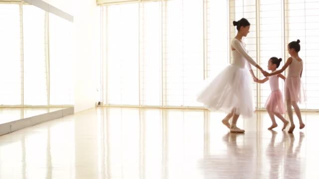 ws ballerina dancing with younger ballerinas. - ballettstudio stock-videos und b-roll-filmmaterial