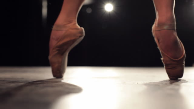 vídeos de stock, filmes e b-roll de cu ballerina feet on point and 'changement de pieds', moving in front of camera under stage lights / new york city, new york, usa - focus on foreground