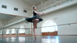 Ballerina in black tutu and pointe stretches on barre in ballet gym. Woman standing near bar and mirror, preparing for perfomance