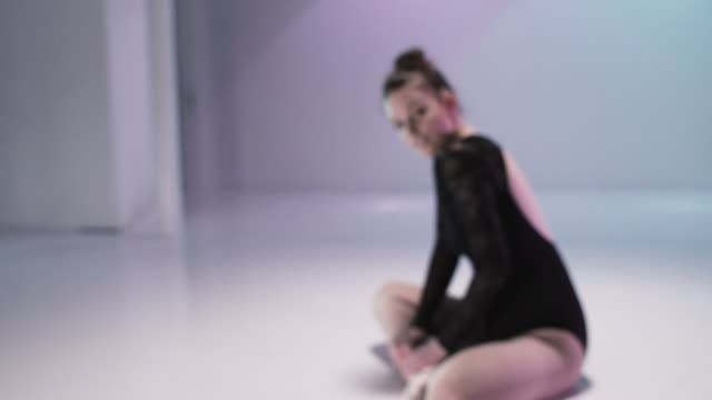 ballerina is sitting in a colorful studio on the ground - sitting on ground stock videos & royalty-free footage