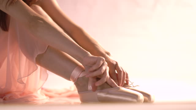 ballerina puts on pointe ballet shoes and tying up her ballet pumps - ballet dancer stock videos & royalty-free footage