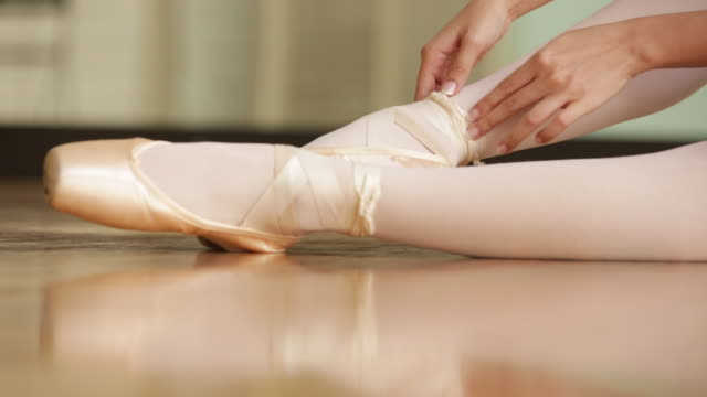 cu ballerina putting on her ballet shoes. - ballet shoe stock videos and b-roll footage