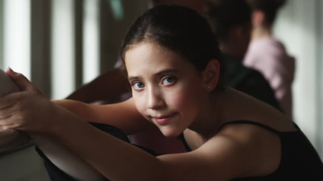 vidéos et rushes de ballerina stretching and looking at camera - une seule petite fille