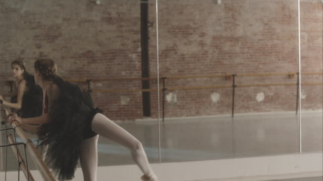 ballerina stretching at ballet bar in dance studio - in front of stock videos and b-roll footage