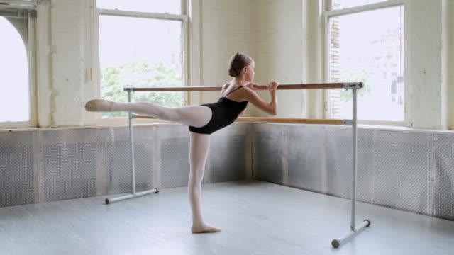 ballerina stretching at barre - auf einem bein stock-videos und b-roll-filmmaterial