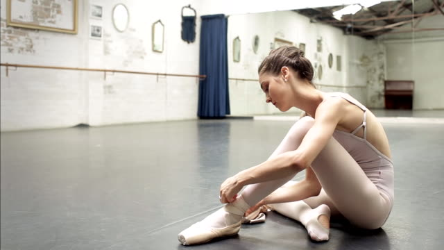ballerina ties up her pointe shoes - wide shot - ballet shoe stock videos and b-roll footage