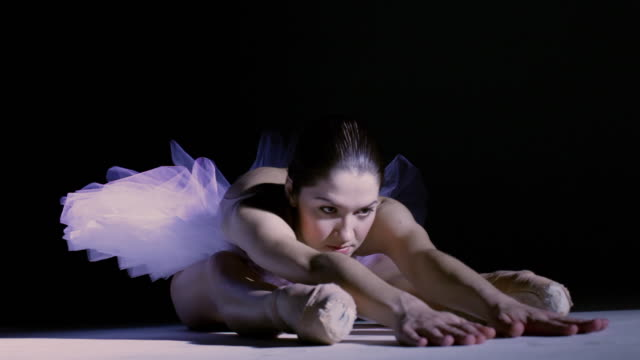 ws ballerina wearing tutu sitting with legs stretched out under spotlight forward bending preparing for performance / new york city, new york, usa - ballet shoe stock videos and b-roll footage