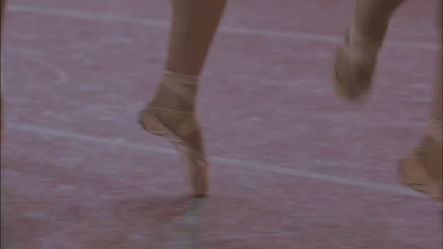 ballerinas dance across a floor in a ballet shoes. - auf den zehenspitzen stock-videos und b-roll-filmmaterial