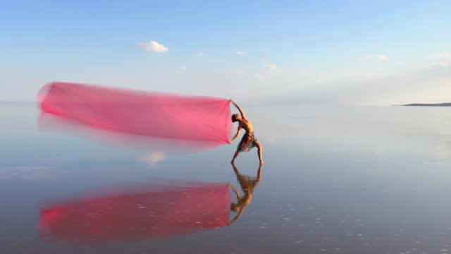 vídeos de stock, filmes e b-roll de bailarinas dançando na água com tule rosa. movimento borrado. - arte, cultura e espetáculo