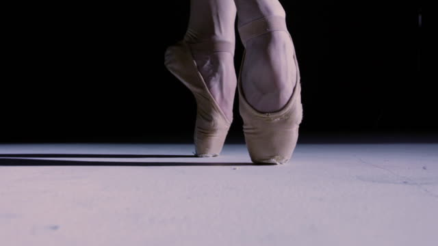 CU Ballerina's feet on point moving in and out of darkness and towards the camera under spotlight / New York City, New York, USA