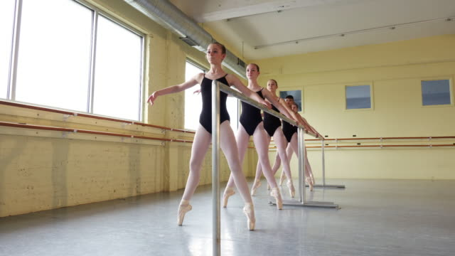 ballerinas practicing at the barre - ballettstange stock-videos und b-roll-filmmaterial
