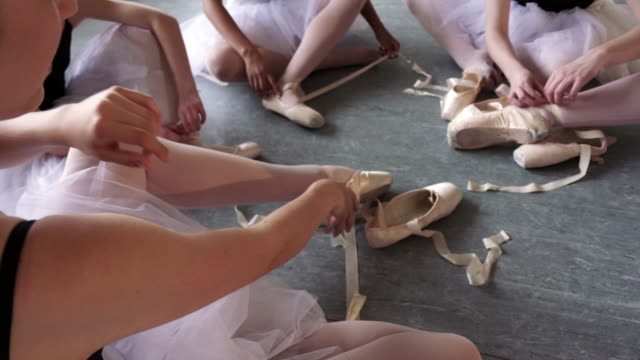 vídeos de stock e filmes b-roll de ballerinas sitting on floor removing pointe shoes - estúdio de dança