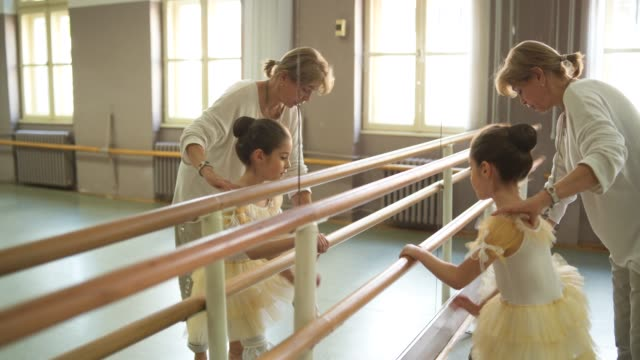 ballet coach helping little ballerina to stretch - ballet performance stock videos & royalty-free footage