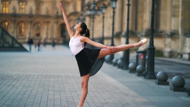ballet dancer amanda derhy performs a 'attitude', wears a white leotard, repetto ballerina shoes and a light purple skirt, in front of the louvre... - leotard stock videos & royalty-free footage
