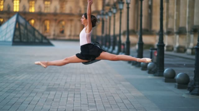 vídeos de stock e filmes b-roll de ballet dancer amanda derhy performs a 'grand jete' wears a white leotard repetto ballerina shoes and a light purple skirt in front of the louvre... - body de ginástica