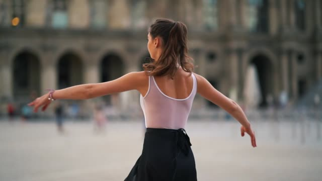 vídeos de stock e filmes b-roll de ballet dancer amanda derhy performs a 'pirouette' wears a white leotard repetto ballerina shoes and a light purple skirt in front of the louvre... - body de ginástica