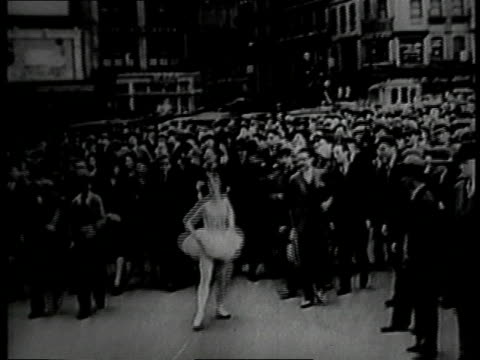 1930 montage ballet dancer dancing down the middle of the street with a crowd following her / new york, new york, united states - 1930 stock-videos und b-roll-filmmaterial